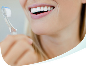 Woman Smiling, Showing White Teeth and Holding a Toothbrush Thumbnail
